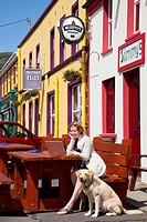 A woman sits at an outdoor table working on her laptop computer with her dog sitting next to her, allihies county cork ireland