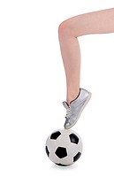 female foot in shoe is on the soccer ball