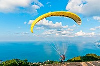 Yellow paraglide on the top of the hill