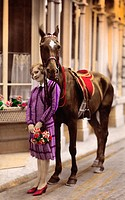 Young woman standing on the road with horse , At 1920 , beautiful woman portrait in purple dress, standing on the street with a horse and fashionable ...
