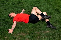 Man exercising and stretching on grass in the sunshine