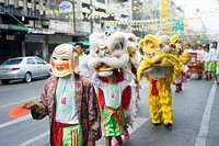 Bangkok, Thailand _ March 27, 2011: Young boys are clothed in brightly coloured costumes walking in a lively procession throw Bangkok street on their ...