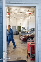 Hispanic worker walking in auto repair shop