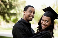 Man hugging college graduate girlfriend