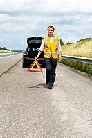 Motorist, carrying a warning triangle, placing it at a safe distance from his broken down car along a motorway