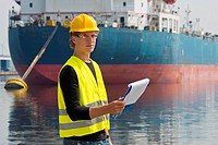 Docker looking up from his notes, standing in front of a large container ship