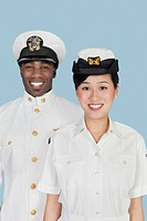 Portrait of multi_ethnic US Navy officers smiling over light blue background