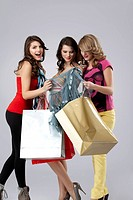 young women looking happy shopping bags
