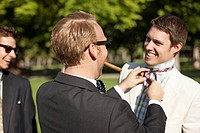Caucasian man fixing friend´s tie