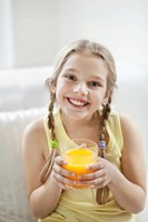Portrait of happy young girl drinking orange juice