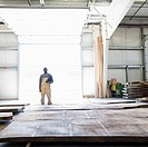 Black worker standing with lumber in warehouse