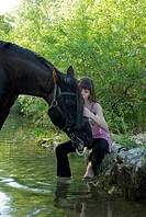 child and horse in river