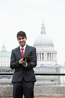 Portrait of a happy Indian businessman using tablet PC against St. Paul´s Cathedral