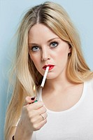 Portrait of young blond woman igniting cigarette against light blue background