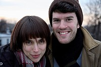 A young couple side by side, outdoors in cold weather
