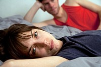 A young unhappy couple lying in bed