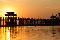 Silhouette of people crossing U Bein Bridge at sunset, Amarapura, Burma