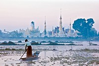A man rowing a boat towards a temple in Burma