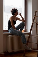 A woman sitting on a window sill and resting her foot on a ladder