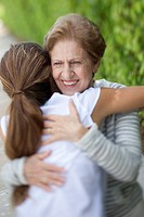 A senior woman hugging a young woman