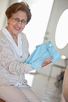 A senior woman holding a blue baby t_shirt