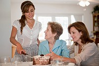 A young woman serving cake for her mother and grandmother