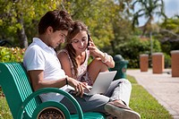 A young couple sitting on a park bench using a laptop and mobile phone (thumbnail)