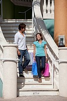 A young couple walking down stairs carrying shopping bags