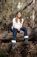 Girl sitting on tree trunk in Mooresville, North Carolina, USA