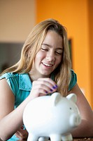 Girl putting coin in piggy bank (thumbnail)