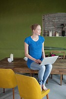 A woman sitting on her dining table using a laptop