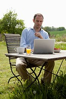 A man sitting at a table in his backyard having breakfast and using a laptop (thumbnail)