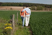 A couple walking side by side in a field, rear view