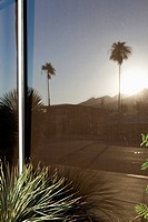 Reflection of mountains, palm trees and a house in a window
