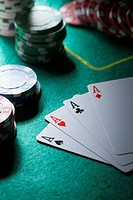 A hand of cards displaying four aces, gambling chips in background