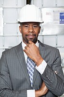 Portrait of an African American male contractor standing with hand on chin