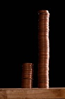 Two different sized stacks of copper coins side by side