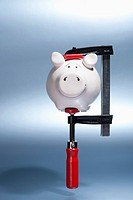 A piggy bank being held in a vise grip suspended in mid_air