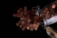 A glass jar spilling copper Euro coins