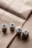 Lettered cubes spelling SELL lying on top of a financial page