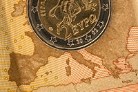 Detail of a fifty Euro banknote with a two Euro coin on top of it