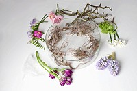 Flowers lying on a table around a glass bowel vase (thumbnail)