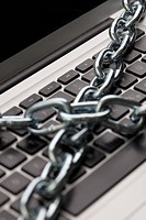 A thick metal chain wrapped around a laptop, close_up