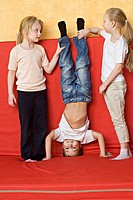 Two girls holding a boy upside down (thumbnail)