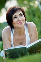 A mature woman lying down on grass with a book (thumbnail)