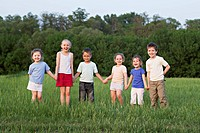 Children holding hands and standing in a field