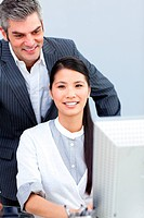Asian businesswoman and her ma ger working at a computer