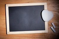 A small blank chalkboard with chalk and a heart shaped eraser