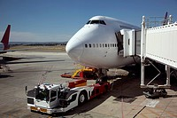 Jumbo jet attached to boarding bridge with tug in front (thumbnail)