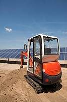 Digger on solar panel construction site